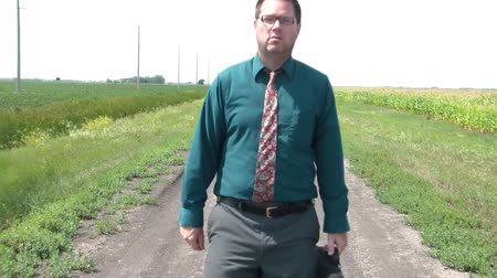 tüyler : Businessman in necktie walks down dirt road towards camera, stops and pulls out paper in business shirt, and then unfolds paper reading help need biz leads.