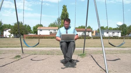 irony : Businessman swinging at playground with laptop computer on legs, typing keys while swing rocks him gently, then stops and walks by, in sunlight.