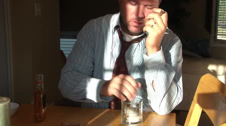související : Businessman with shirt and necktie lights cigar, places ice cubes into glass, and pours whiskey from a bottle and ponders his existence after a long workday. Dostupné videozáznamy