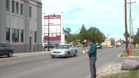 gravata : Businessman takes a picture and then writes down information about building on paper at edge of road in sun, and then walks past camera.