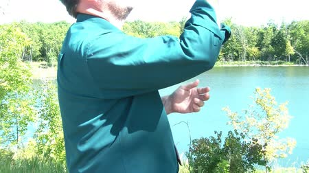 deli : Frustrated businessman throws phone in lake after not receiving cell reception in rural Minnesota area. Stok Video