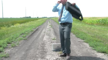 irony : Businessman in sun stands on dirt road with laptop computer, walks in circles on phone, slams case to ground, kicks dirt, and then closes phone in pure frustration.