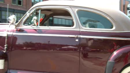 Gorgeous vintage chevy special deluxe that has a shiny maroon body, classic white wall tires, and a white soft top roof.