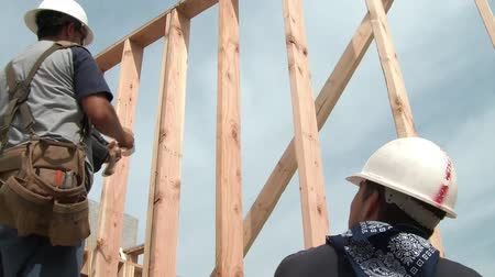 martelo : Construction worker uses a air powered nail gun and swings a hammer at a stud on new wood framing.