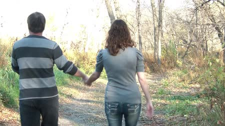 общаться : Couple walks in the fall season together, holding hands and talking down a wooded dirt road near river bank in afternoon.