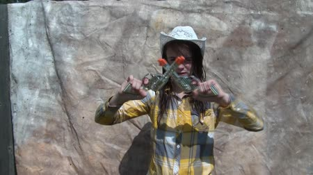 liquidação : Young cowgirl shoots toy guns at camera with fake teeth in mouth, desert canvas background in sunlight.
