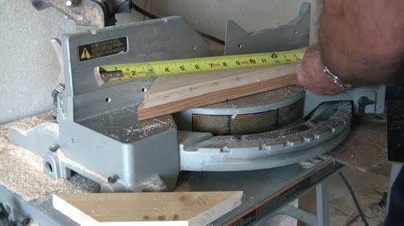 miter saw : Man is cutting wood with table saw, and then utilizes a tape measure to further the additional cuts.