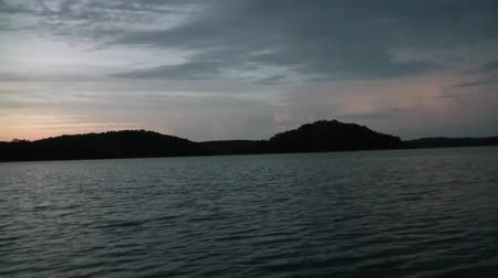 volatile : Calming clip from dock on a lake in summer at dawn with view of hilly landscape in background. Stock Footage