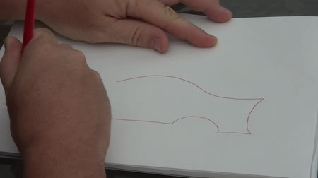 estético : Hand begins drawing a sports car on paper in red ink with natural outdoor lighting above and finishes with muffler.
