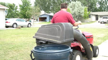 lixeira : Guy stops red lawn tractor to unload grass from bagger into garbage can, in natural sunlight.