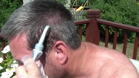 борода : Man is dying grey hair in the sunlight with a comb in instrument and then considers putting dye into beard at very end. Стоковые видеозаписи