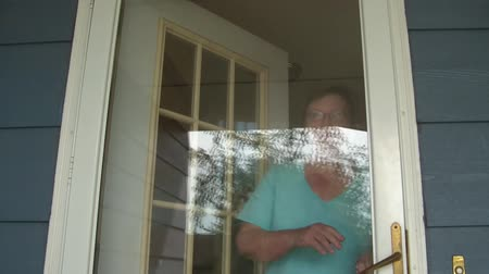 přední : Older lady answers her door and then proceeds waving gesture to come into her home.