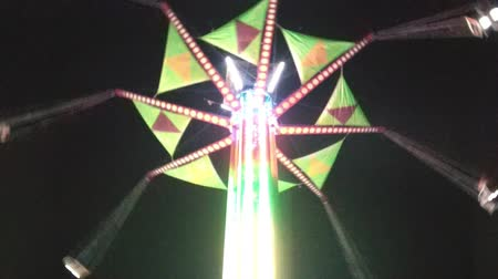 targi : Fair swings twist in circle above with stem lighting up while camera pans downward to the rest of the amusement rides on ground.