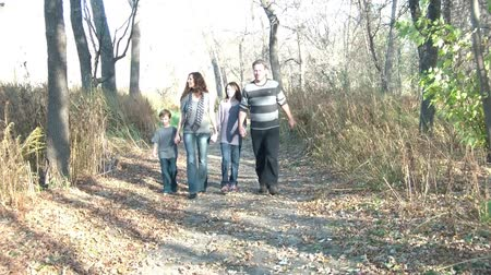 родной брат : Family of four walks through woods in autumn down a dirt road, and holding hands past camera at sunset.