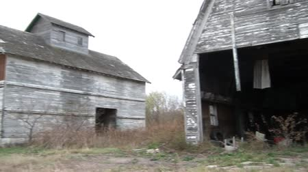 asal : Pan of farm in ruins with dilapidated wood siding and paint, starting from farmhouse, and ending at old barn hayloft doors. Stok Video
