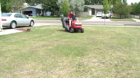 trawnik : Father and son ride together on red lawn tractor towards camera and in front, in summer sunshine.