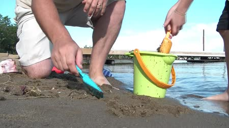 sandy waters : Father and son dig in beach sand to put into green bucket on summers afternoon with colored plastic shovels at edge of lake.