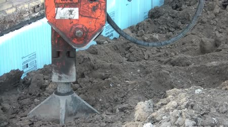 давление : Jackhammer with flat bottom pounds dirt by compressing it downward in afternoon sunlight.