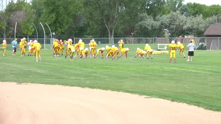 empilhamento : Youth football team practices by scrimmaging each other with colored helmets, in natural lighting.