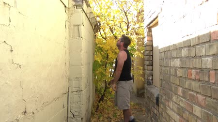 volatile : Severely frustrated man kicks, slaps, flails arms, and is emphatically talking towards wall in alley during autumn.