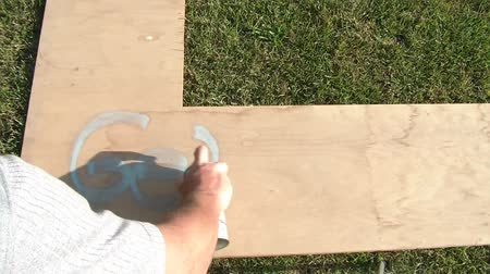 üdvözlettel : Get well sprayed in paint on wooden board in sun with green grass as background.