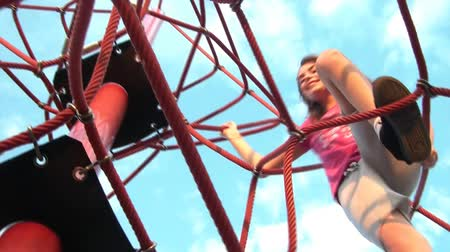kurs : Girl climbs ropes obstacle to the top during sunset, shot from below. Wideo