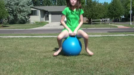 gramado : Young girl hops by sitting and bouncing on blue ball in yard towards camera, and then passes, on sunny afternoon.
