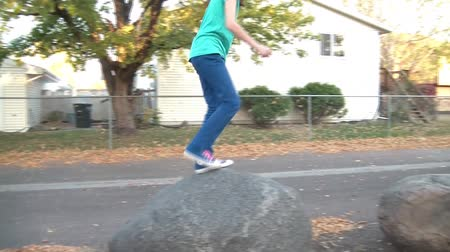 onto : Girl jumps onto large rocks in the fall season and makes her way down a line of them until almost finishing.