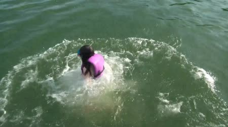 respiração : Girl jumps into lake water with mask on face during summer vacation in sunlit conditions. Vídeos