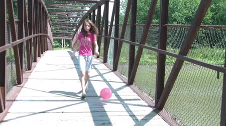 executar : Girl kicks pink ball over bridge while running after it in sunlight, reaching cement entrance to park at end.
