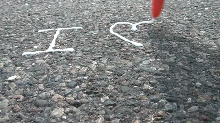 namorado : White glue is applied to blacktop road reading I love you, with love represented as a heart symbol, and you with letter u.
