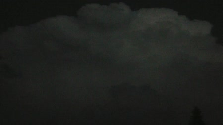 charged : Pan of large white storm cloud at night with sporadic illuminations of dry lightning as camera moves from side to side. Stock Footage