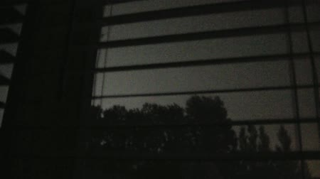 rolety : Lightning strikes abundantly through white window blinds in darkened room during summer night.