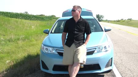 sem problemas : Man leaning on front of blue car on roads shoulder looking as if stranded or ran out of gas in rural america.