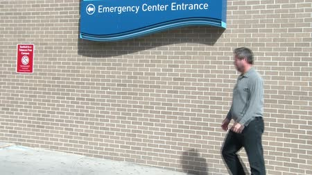 kolano : Man is limping into emergency room entrance at hospital on sunny afternoon. Wideo