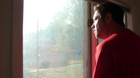 perceive : Man looking out window pondering, wearing bright red shirt, in natural lighting. Stock Footage