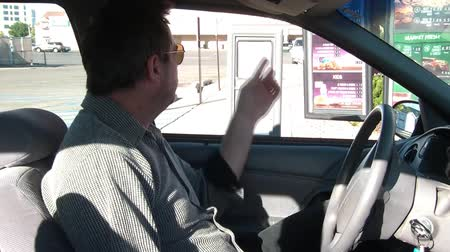 fry : Man orders food at drive through, shot from passenger side past man, and towards sign board, in morning sun. Stock Footage
