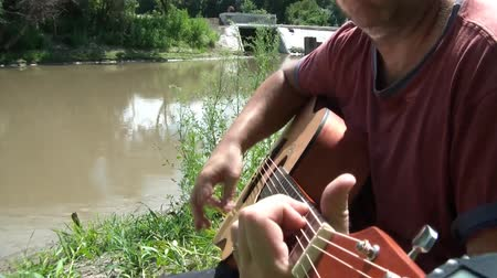 yazarak : Man strums and picks his acoustic guitar on river bank in summer sunshine.