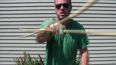 significar : Man uses bamboo stick to swing back and forth at camera only to slam it into hand at end and make a mean face. Vídeos