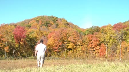 kopec : Man walks into autumn forest after waving towards camera to come with, in angled morning sunlight.