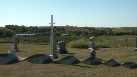 saygı : Rural cemetery in central North Dakota with old wire fencing moving in the harsh winds and rolling hills in background.