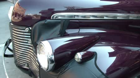 panned : Panning of a shiny classic purple car in shaded lighting from fender, to grille, and back down drivers side.