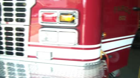 panned : Clip of fire station including rescue raft, fireman, and front of red fire truck in natural lighting. Stock Footage