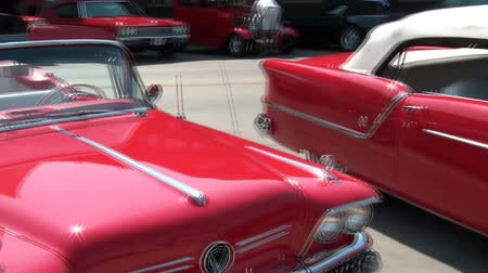 antika : Pan of classic red cars in sunshine with maximum reflection from paint and chrome.