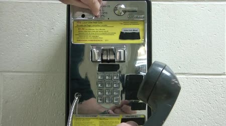 earpiece : Hand picks up pay phone, inserts quarter into coin slot, and then proceeds to dial various numbers before bringing phone towards camera at end. Stock Footage