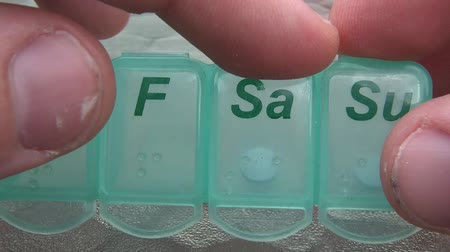 separado : Fingers calculate days by counting onto blue plastic pill organizer before opening up the saturday reading sa compartment, emptying blue pill, and then picking up for consumption.  Vídeos