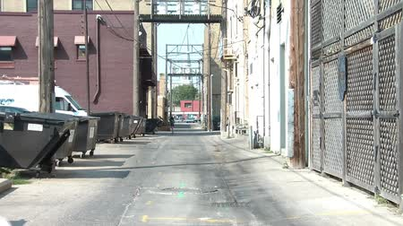 uliczka : Abstract of pink balloon drifting past camera in downtown alleyway, bouncing along pavement in bright sun.
