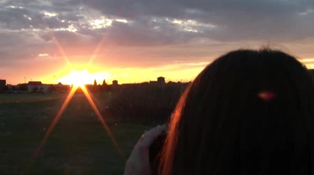 natura : Girl taking pictures of sunset, shot from behind, stepping away towards end. Wideo