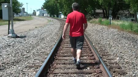perdido : Man in red shirt walking away from camera down railroad tracks in summer.  Vídeos