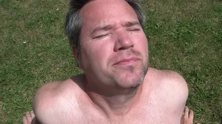 skóra : Man with half shaved beard tans face outside while leaning back in grass, in the summer sunlight.